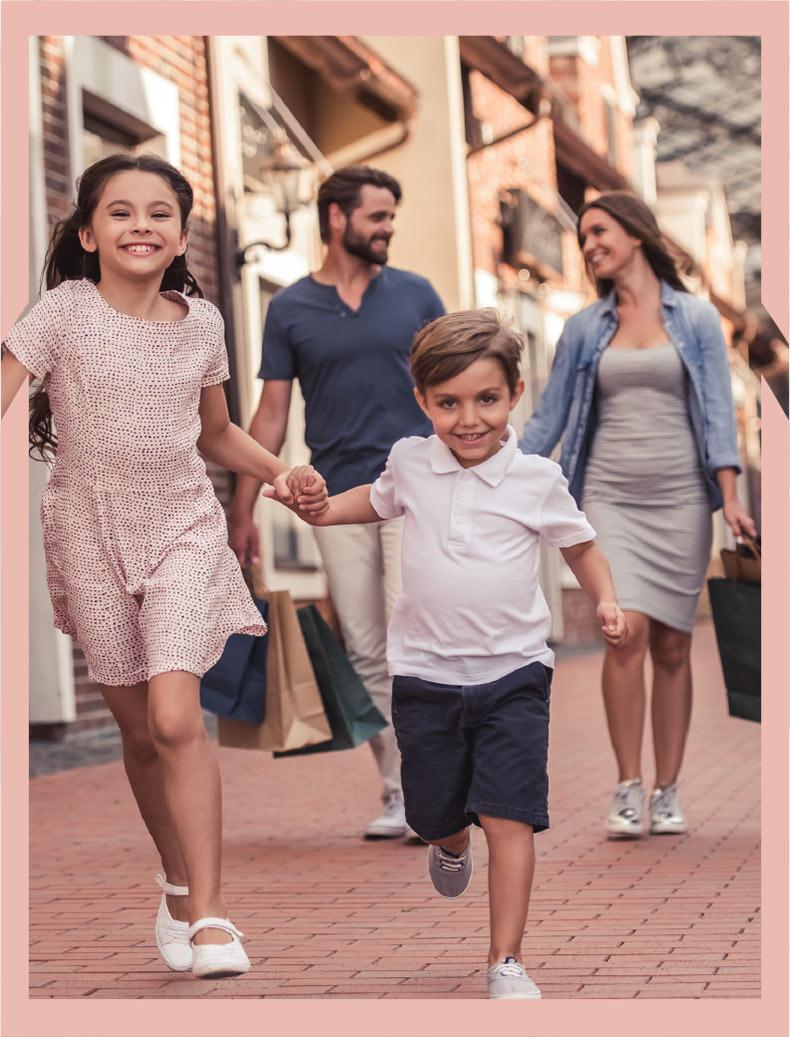 Happy family walking down sidewalk in front of shops